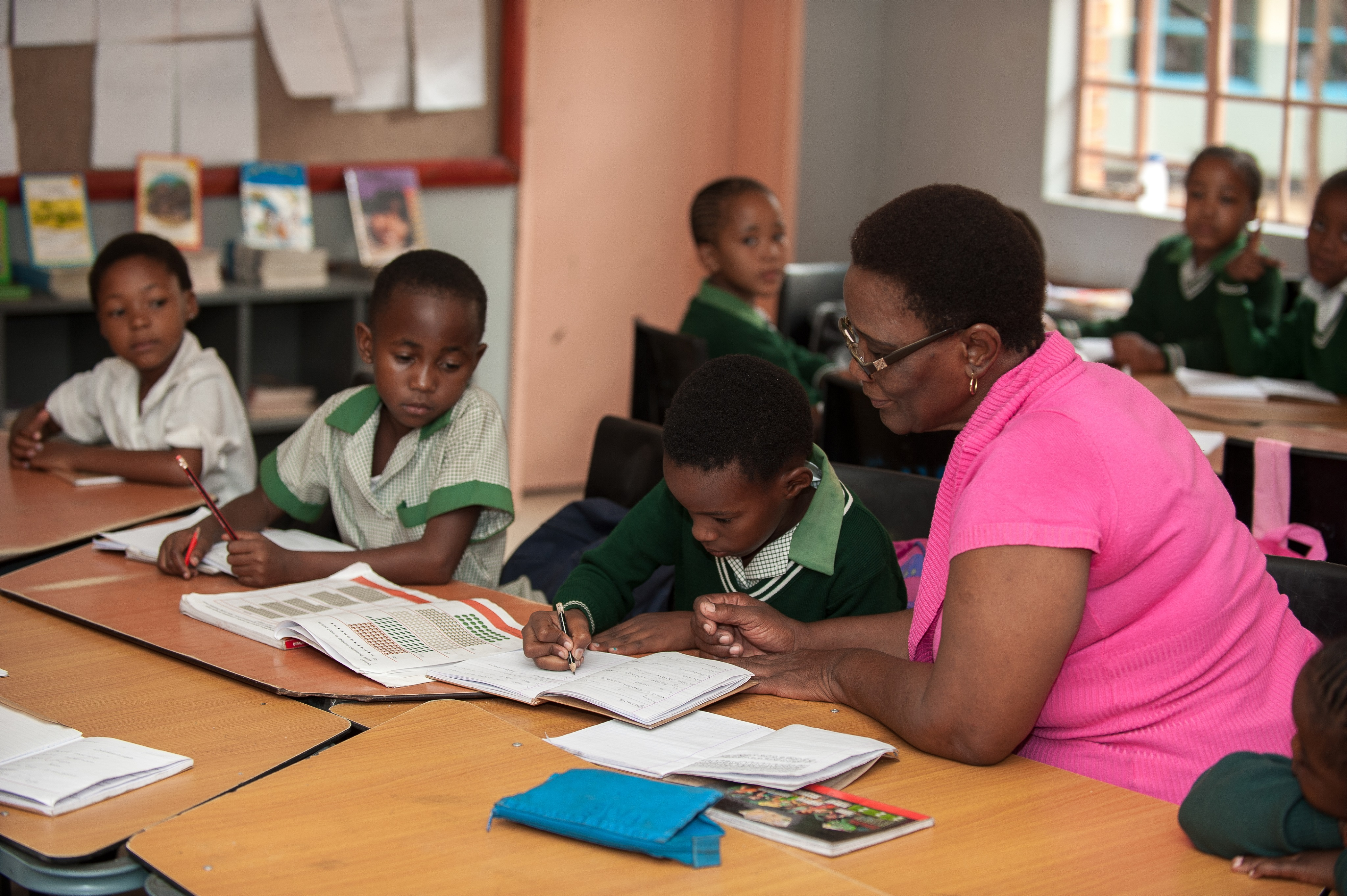 African teacher reading with students